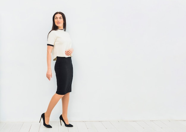 Mujer joven en el traje de falda que se coloca en el fondo blanco de la pared
