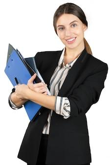 Mujer joven en traje formal sosteniendo una pila de documentos aislados sobre fondo blanco.