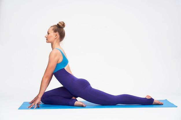 Una mujer joven, en un traje de gimnasia, realizando un ejercicio en un gimnasio.