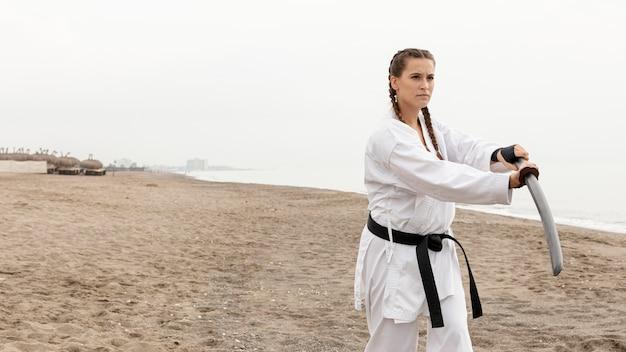 Mujer joven en traje de karate al aire libre