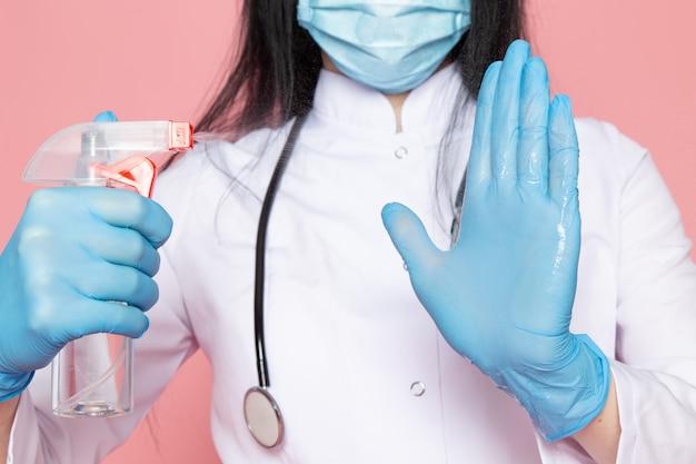 Mujer joven en traje médico blanco guantes azules máscara protectora azul con estetoscopio con spray desinfectante en rosa