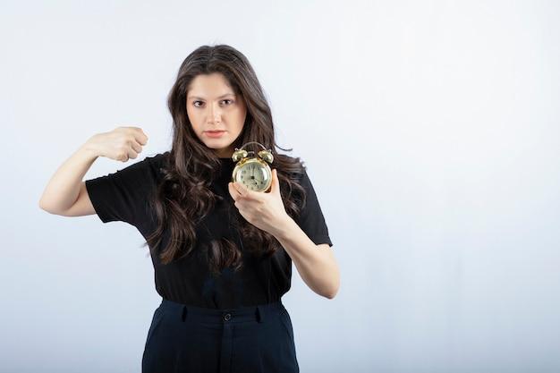 Mujer joven en traje negro con ganas de perforar el despertador.