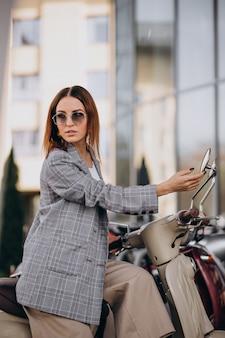 Mujer joven en traje de pie junto a la moto