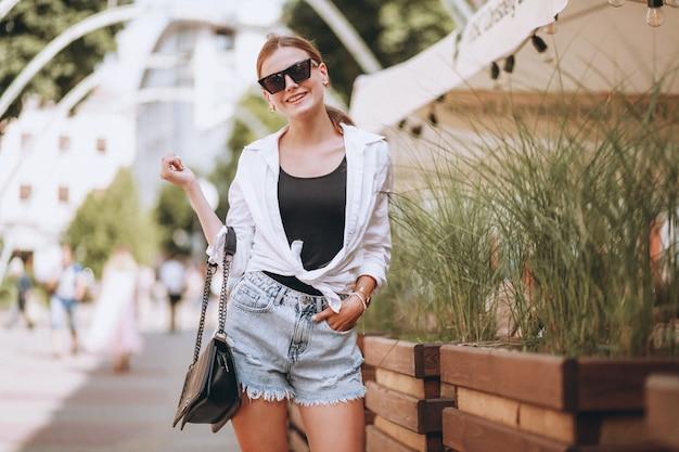Mujer joven en traje de verano en la ciudad