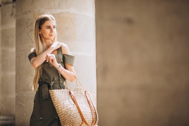 Mujer joven en traje de verano por un edificio antiguo