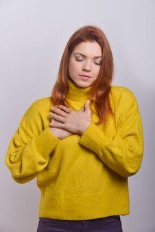 Mujer joven tranquila con las manos en el pecho