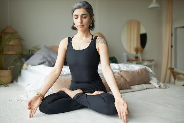 Mujer joven tranquila y pacífica con cabello gris, anillo en la nariz y tatuaje manteniendo los ojos cerrados mientras practica la meditación después del yoga