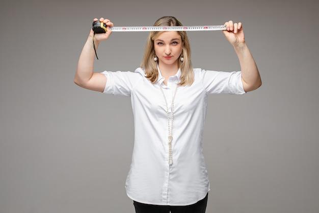 Mujer joven tranquila de pie sobre la pared gris y poniendo una cinta métrica sobre su cabeza