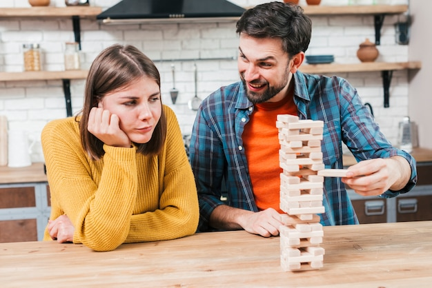 Mujer joven trastornada que mira al hombre feliz que juega la pila de madera en el escritorio