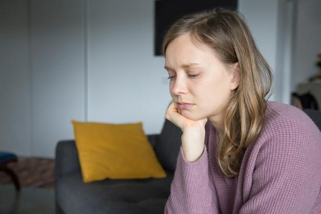 Mujer joven trastornada que se sienta en el sofá en casa, mirando abajo