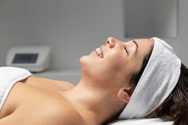 Mujer joven con un tratamiento de cuidado de la piel facial