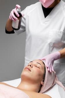 Mujer joven con un tratamiento facial en el salón de belleza