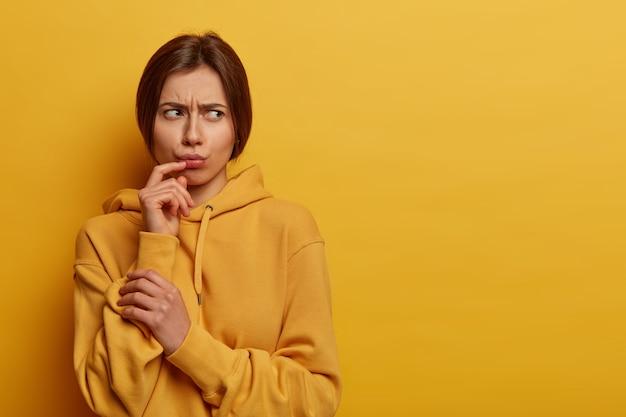 La mujer joven triste y disgustada piensa en algo problemático y perturbador, mira con enojo a un lado, hace pucheros en los labios, frunce el ceño, vestida con una sudadera con capucha informal, aislada en la pared amarilla. sentimientos negativos