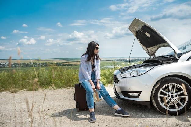 Mujer joven triste y esperando ayuda cerca del coche dañado.