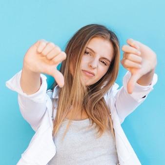 Mujer joven triste que muestra los pulgares hacia abajo delante de la cámara contra el fondo azul