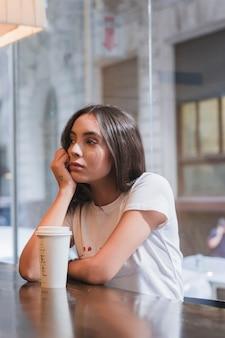 Mujer joven triste que se sienta en café con la taza de café para llevar en la tabla de madera