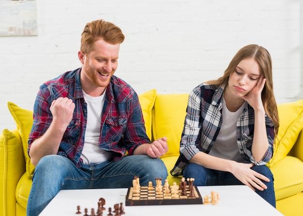 Mujer joven triste que se sienta con su novio que anima después de ganar el juego de ajedrez en casa