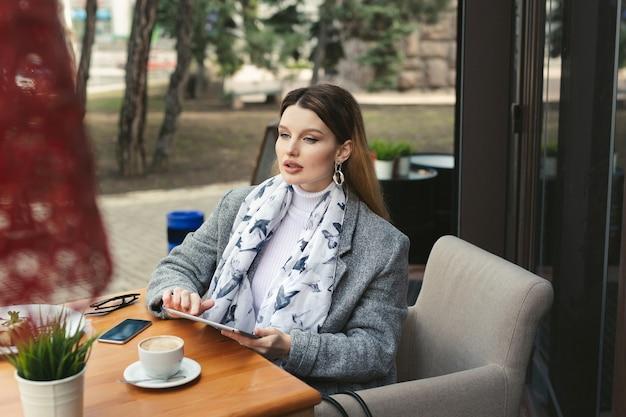 Mujer joven triste con una tableta en un café