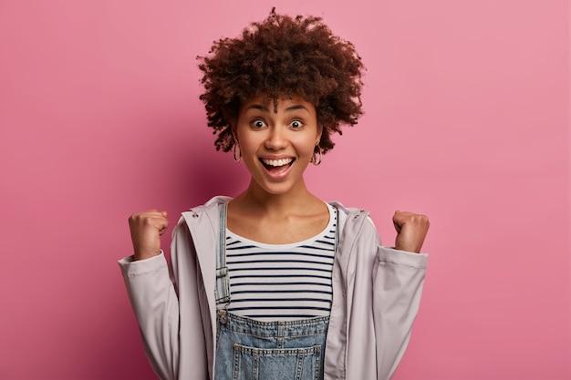 Mujer joven triunfante exagerada con peinado rizado, aprieta los puños y exclama con alegría, tiene una amplia sonrisa, se regocija por el éxito, usa un jersey de rayas, anorak casual, posa sobre una pared rosa
