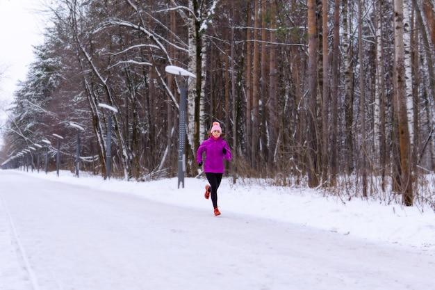 Mujer joven trotar en un callejón cubierto de nieve en un día de invierno