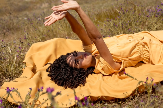 Mujer joven tumbada en tela amarilla en la naturaleza