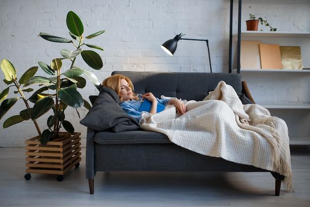 Mujer joven tumbado en un sofá acogedor y leyendo un libro