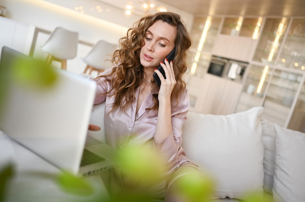 Mujer joven tumbado en un sofá blanco en el interior de la cocina de la sala de estar, hablando de teléfono inteligente y trabajando en un ordenador portátil.