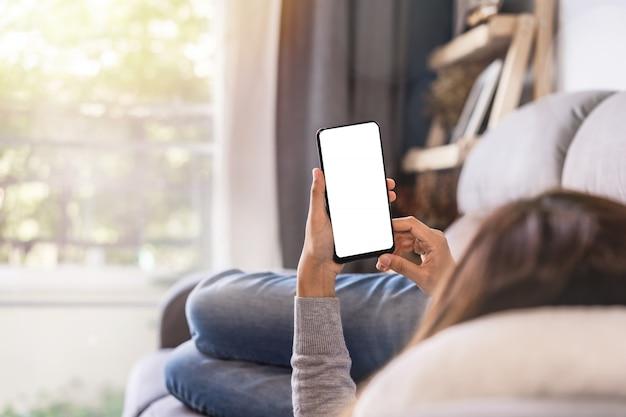 Mujer joven tumbado en el sofá en la sala de estar y utilizando el teléfono celular en casa