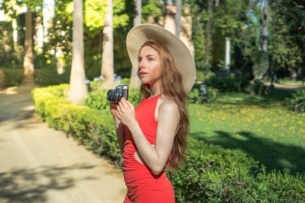 Mujer joven de turismo con una cámara en sus manos turista tomando fotografías durante sus vacaciones