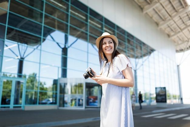 Mujer joven turista alegre viajero sosteniendo cámara de fotos vintage retro, mirando a un lado en el aeropuerto internacional