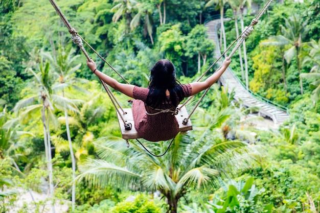 Mujer joven turista balanceándose sobre la selva tropical en la isla de bali