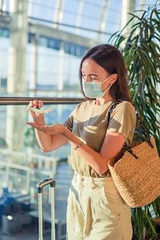 Mujer joven turista en máscara médica con equipaje en el aeropuerto internacional