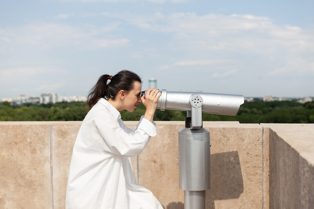 Mujer joven turista de pie en la azotea del edificio mirando a través del telescopio