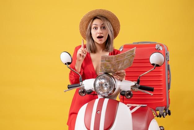 Mujer joven turista con scooter y mapa apuntando hacia arriba