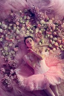 Mujer joven en tutú de ballet rosa rodeado de flores