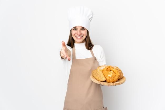 Mujer joven en uniforme de chef aislado en blanco apretón de manos después de un buen trato