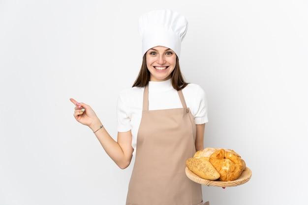 Mujer joven en uniforme de cocinero en el dedo acusador blanco al lado