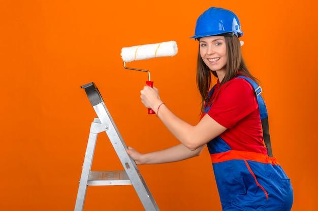 Mujer joven en uniforme de construcción y casco de seguridad azul en escalera sonriendo y sosteniendo el rodillo de pintura sobre fondo naranja