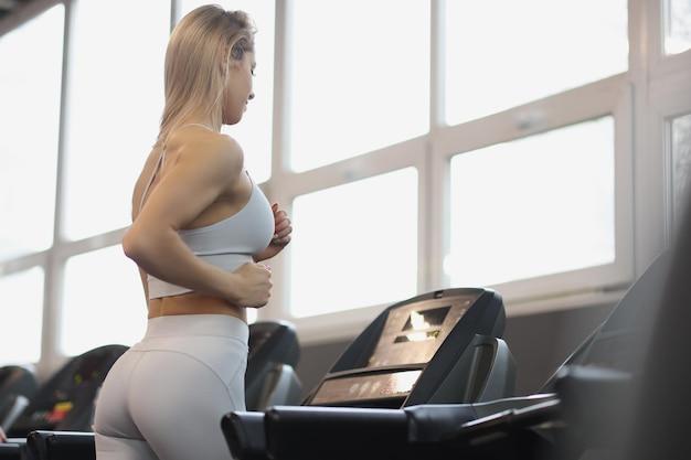 Mujer joven en uniforme deportivo trabajando en cinta en el concepto de entrenamiento deportivo regular de gimnasio