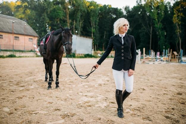 Mujer joven en uniforme de jinete y caballo, paseos a caballo. semental marrón, ocio con animal, deporte ecuestre
