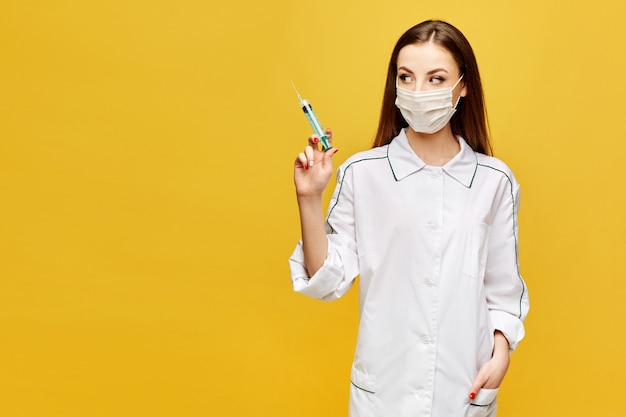 Mujer joven en uniforme médico y máscara protectora mantiene la jeringa médica en la mano y mira a un lado