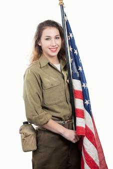 Mujer joven en uniforme militar de estados unidos sosteniendo una bandera estadounidense.