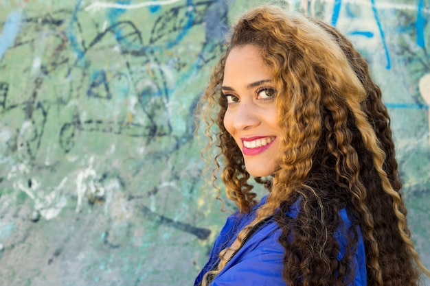 Mujer joven urbana enfrente de muro de grafitti