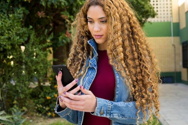 Mujer joven urbana mirando a smartphone