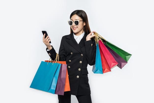 Mujer joven usa gafas y compra en teléfonos inteligentes.