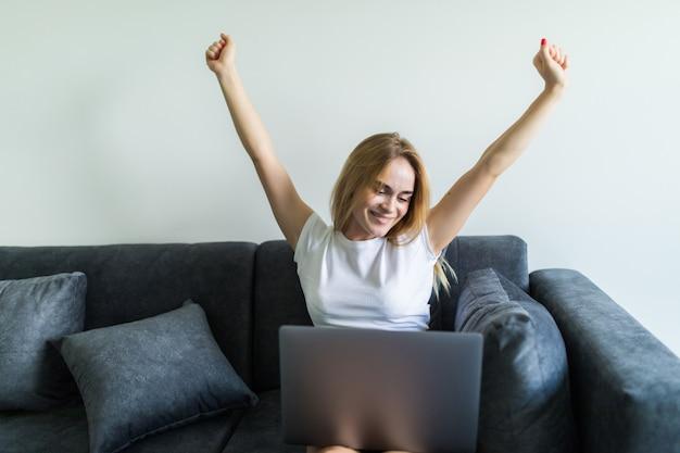 Mujer joven usando una computadora portátil mientras levanta la mano y sentado en el sofá en casa