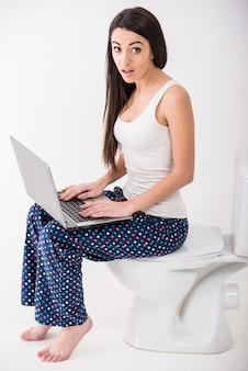 La mujer joven está usando la computadora portátil mientras que se sienta en un retrete.