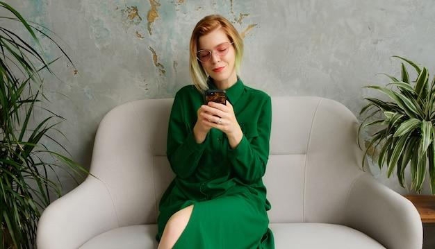 Una mujer joven usando un teléfono móvil, enviando mensajes de texto y jugando juegos móviles. moderno loft interior ecológico.