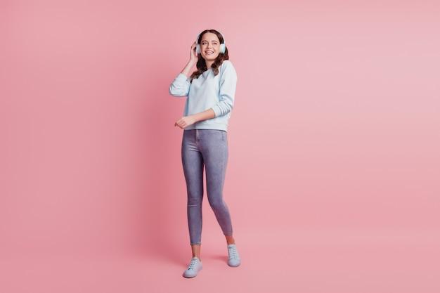 Mujer joven usar auriculares disfrutar de la música buscar sueño de espacio vacío