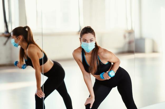 Mujer joven usar máscara y hacer ejercicios en el interior con pesas